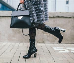 Particolare di ragazza con ecopelicciotto grigio, maxi bag nera e stivali di vernice sempre neri