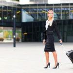 Ragazza che indossa un tailleur nero con camicia bianca e décolleté nere a tacco alto