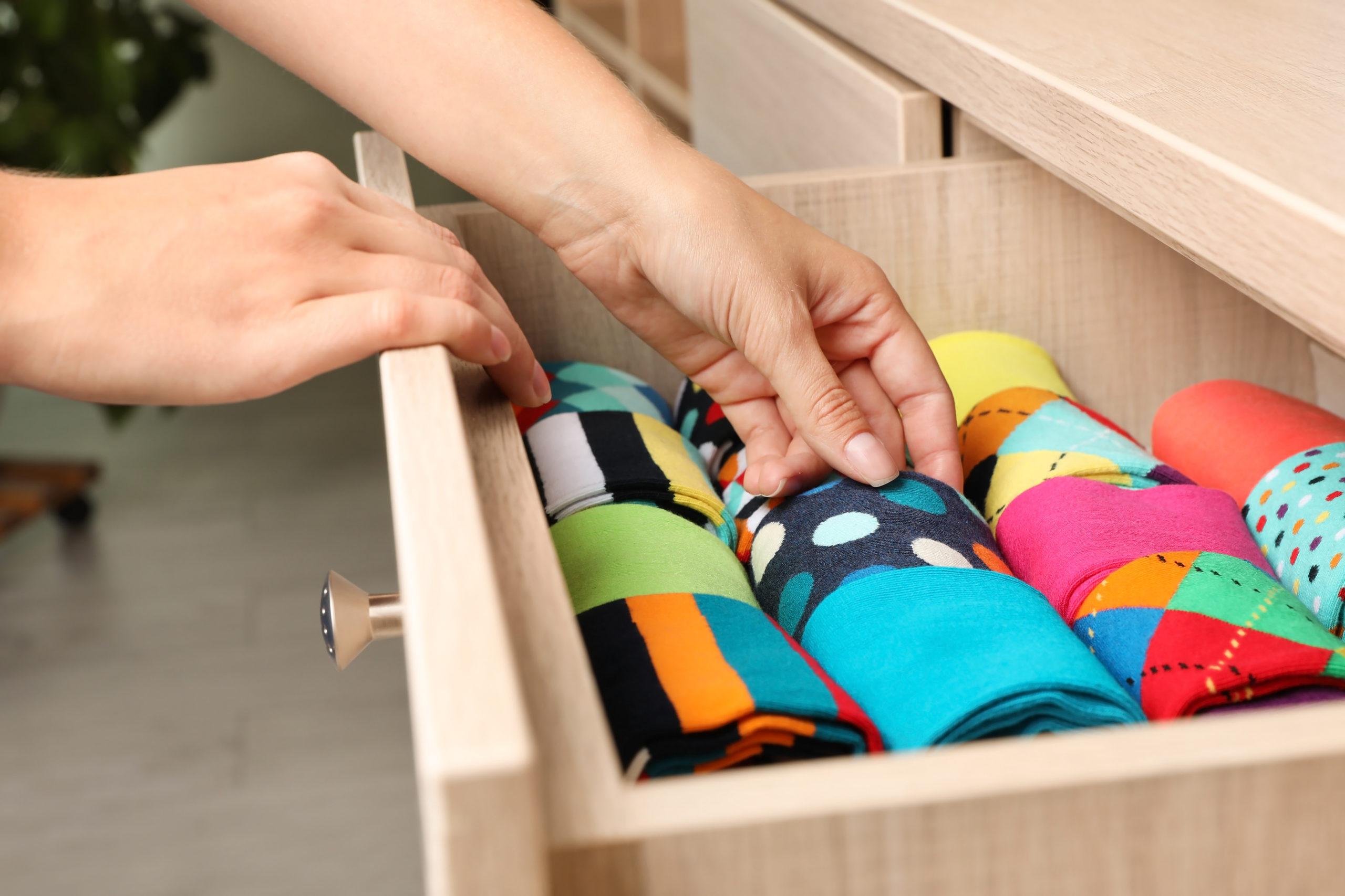 Mani che sistemano ordinatamente le calze in un cassetto