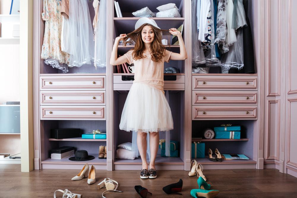 Ragazza felice di fronte al suo guardaroba ordinato e diverse paia di scarpe sparse a terra