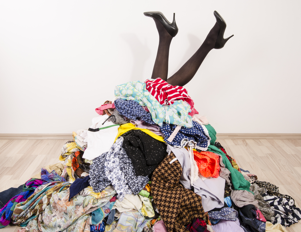 Gambe di ragazza che sporgono da un mucchio di abiti disordinati