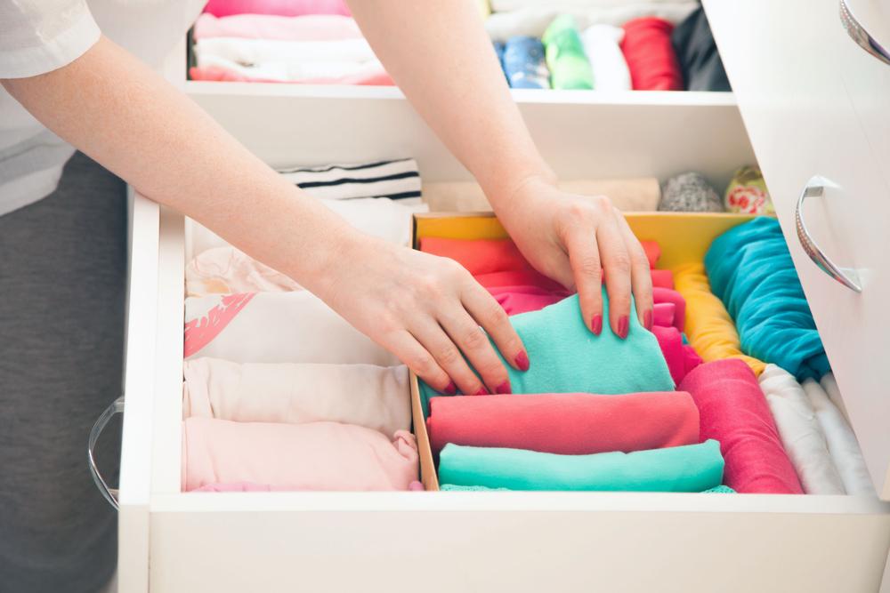 Mani che sistemano abbigliamento vario in un cassetto del guardaroba