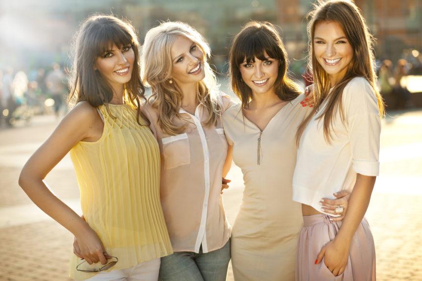 Quattro ragazze che indossano abiti a colori primaverili