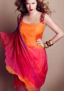 Ragazza che indossa un abito primaverile con spalline gioiello sottili nei toni del rosa scuro e arancio