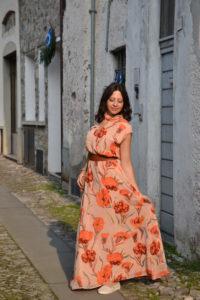 Ragazza che indossa un abito lungo da giorno di colore rosa con fiori arancio e cintura color cuoio