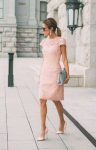 Ragazza che indossa un tubino rosa da cerimonia in pizzo abbinato a pochette color lavanda e decollete a tacco alto in tinta