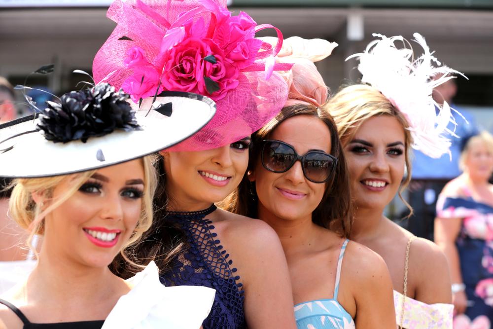 Qauttro ragazze in abiti primaverili da cerimonia. Sono in primo piano e indossano cappellini di forme e colori diversi, tutti adatti a cerimonie
