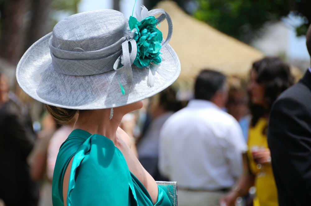 Donna vista di profilo. Indossa un abito turchese da cerimonie completato da un cappellino grigio perla e fiore turchese