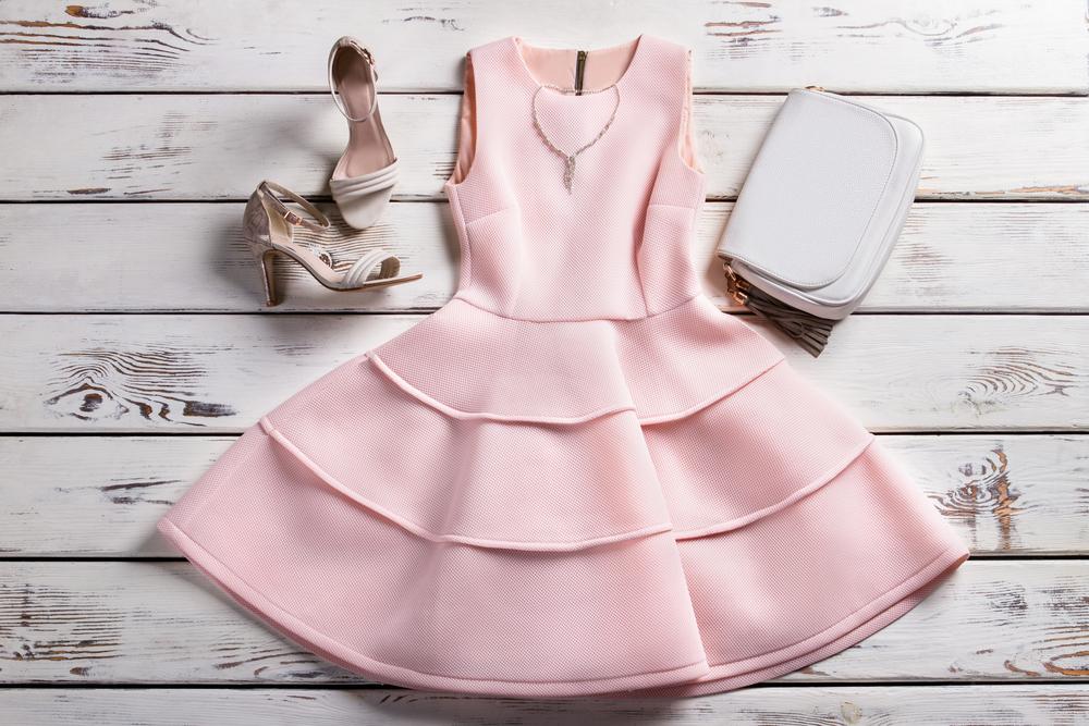 Immagine still life di un completo donna sui toni del rosa. nell'immagine ci sono abito, collier, borsa e scarpe
