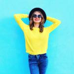 Ragazza che indossa jenas blu e pull giallo lime abbinati a cappello nero e occhiali da sole