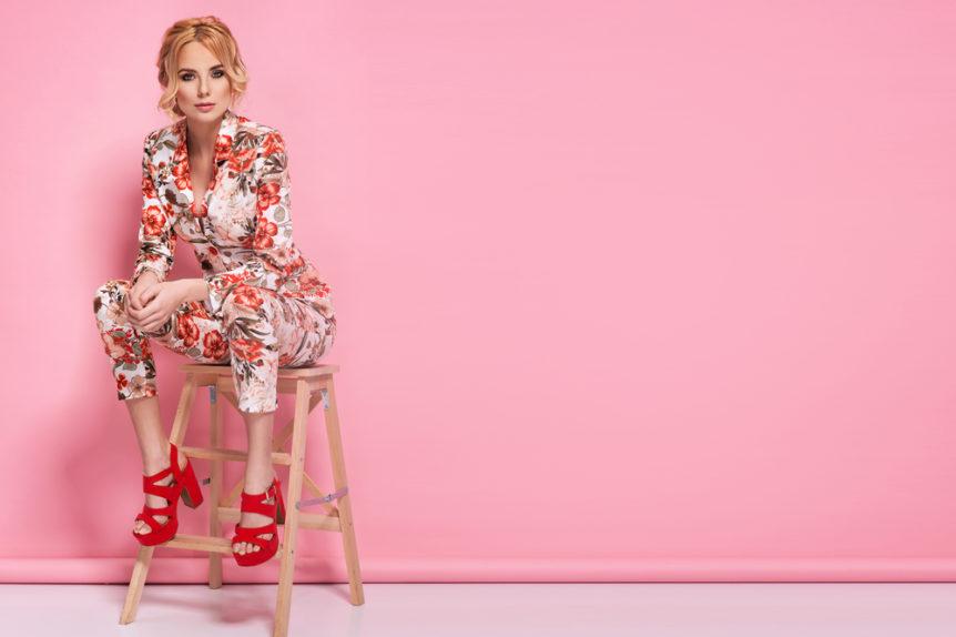 Immagine di una ragazza su fondale rosa. Si trova seduta su uno sgabello in legno e indossa un completo camicia e pantalone sui toni del bianco con decorazioni floreali. Sandali a tacco alto con zeppe di colore rosso