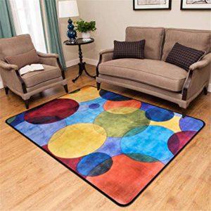 Particolare di salotto con tappeto fantasia a motivi tondeggianti di varie tonalità di colori forti e vivi