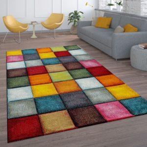 Particolare di salotto con grande tappeto rettangolare a quadrati di diversi colori
