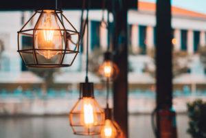 Particolare di lampadari in metallo color bronzo con lampade a vista